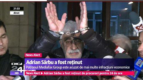 Adrian Sarbu ukazuje na televizní kamery, že skončil v poutech