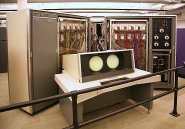 CDC 6600 – v popředí vršek operátorského pultu s vektorovými displeji, v pozadí pak vlastní superpočítač (všimněte si systému chlazení vpravo dole).