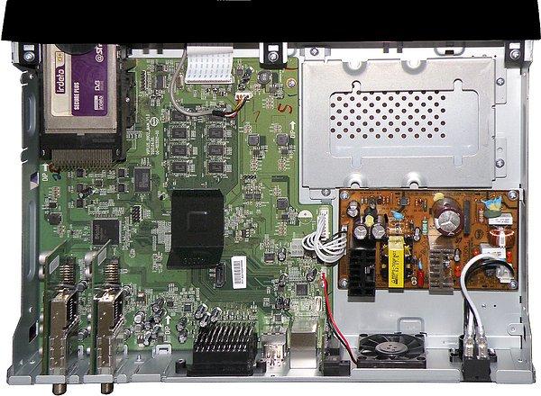 Pohled do přijímače. Vpravo nahoře je připravený prostor pro umístění disků, vpravo dole je zdroj. Všimněte si, že větrák směřuje chlazení právě do těchto míst. Dvoujádrový procesor je chlazen pouze pasivním chladičem, najdete jej uprostřed desky plošného spoje. Dva CI sloty a dvě vestavěné čtečky karet umístěné nad sebou jsou vidět vlevo nahoře. Dva výměnné tunery vidíte vlevo dole.