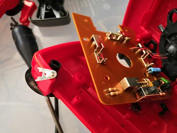 Detail mikrospínače v joysticku. Na plastu se válí odpadlý kontaktní plíšek, pružinka chybí.