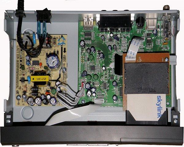 Pohled na chassis přijímače s vloženou přístupovou kartou Skylink Irdeto. Vlevo je plošný spoj usměrňovače, vpravo základní deska přijímače.
