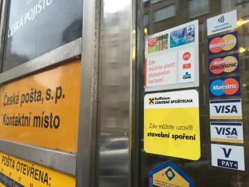 Na loga platebních karet na dveřích klienti pošty čekali přes 20 let. (Pošta Praha 6, 7.10.2015)