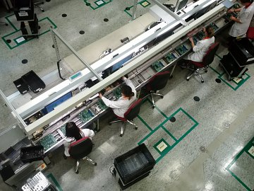 Komponenty jako konektory či baterie na základní desky vkládají lidé.