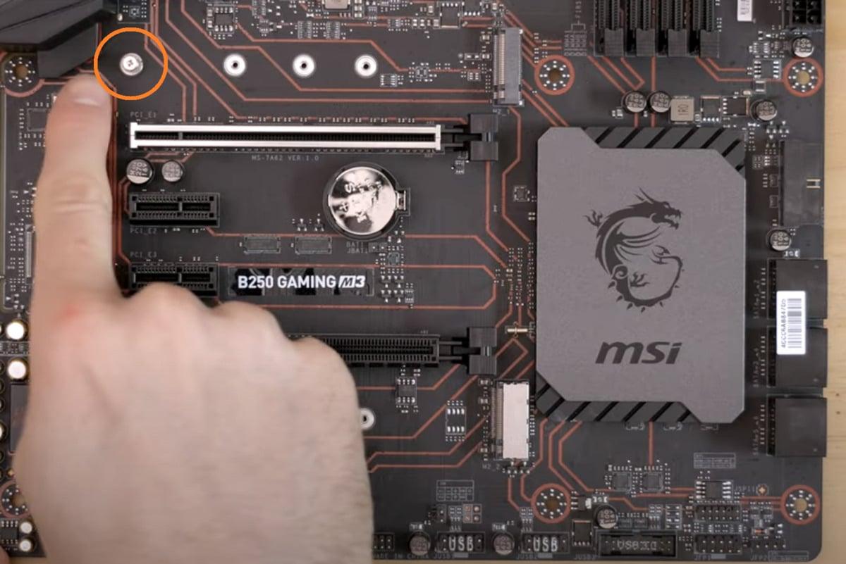 Slot M.2 bude dozajista mít pro instalaci disku SSD v provedení M.2 nějaký systém pro instalaci, například podložku se šroubkem, která je vidět na obrázku v oranžovém kolečku a na kterou ukazuje náš prst. Tato podložka udržuje disk SSD při instalaci na základní desce rovně.