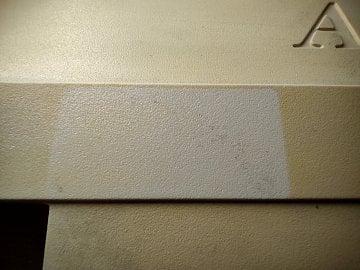 Viditelná stopa po odstraněné samolepce, která bránila UV záření zabarvit plast pod sebou.