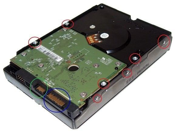 Tento pevný disk je otočený spodní částí nahoru, aby byly vidět jeho části. Na obrázku je červeně zvýrazněno sedm otvorů z celkových deseti – sem se montují šroubky. Modře je označen konektor pro napájení disku a zeleně pak konektor pro datový kabel.