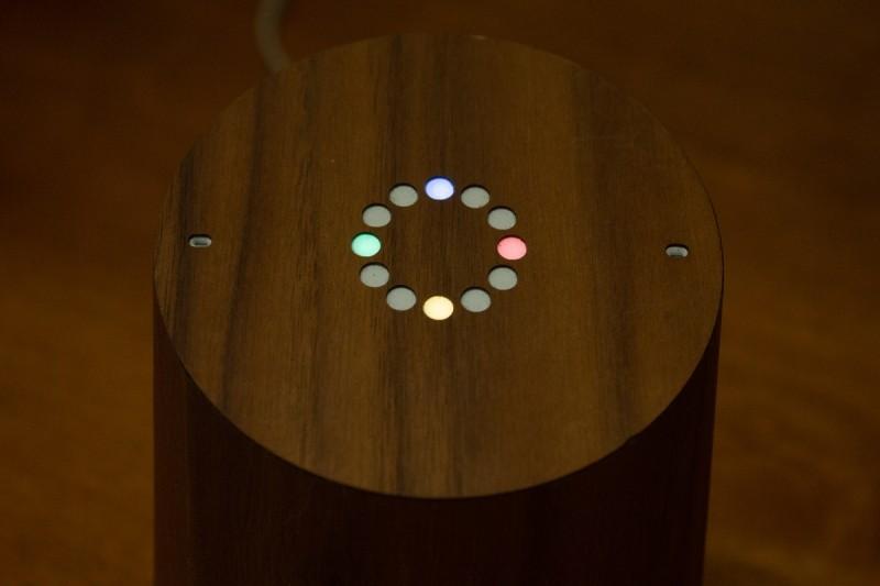 Originální zařízení Google Home v okamžiku, kdy aktivujete Asistenta Google, rozsvítí až čtyři barevné LED diody. Zařízení na obrázku bylo upraveno obalem od firmy Toast imitujícím dřevo.